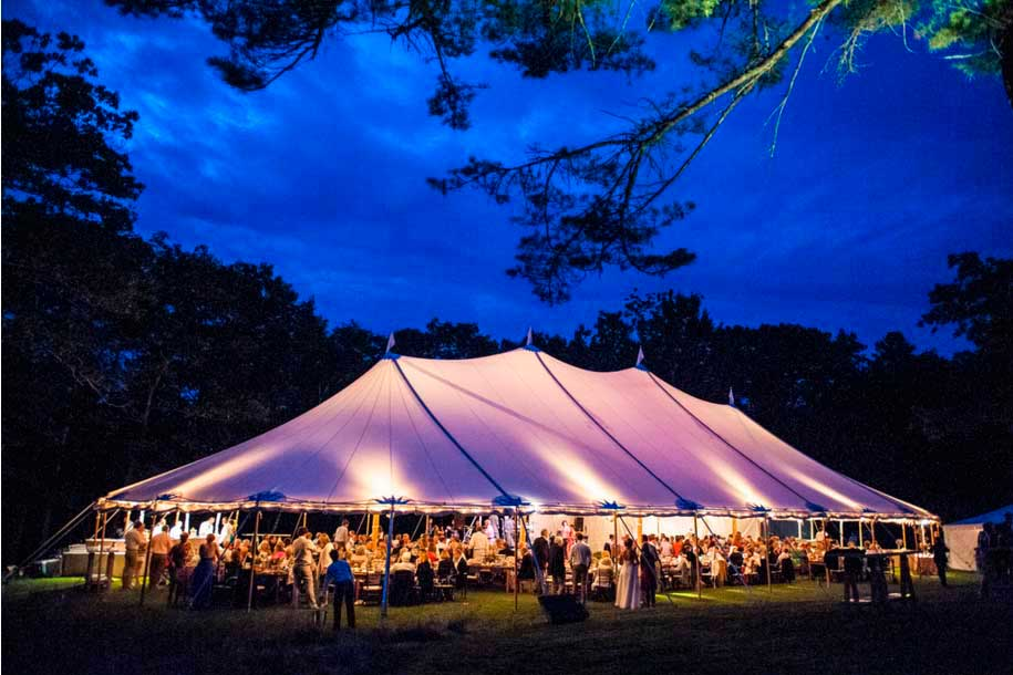A large tent is illuminated at night during a gorgeous Churchill Events outdoor Maine wedding. Photo Courtesy of Andree Kehn http://andreekehn.com