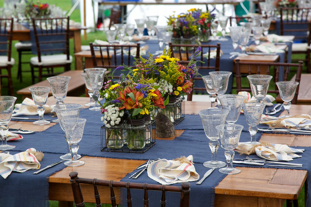 Maine wildflowers and blue linen runners exude casual elegance in this table design at a wedding on the coast of Maine.