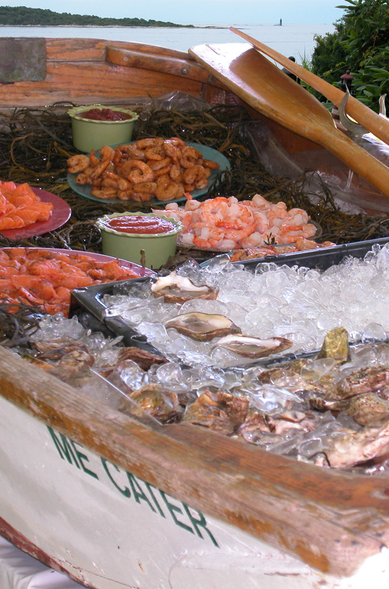 An antique dinghy is used to display a raw bar featuring freshly shucked oysters, steamed and spiced shrimp, and Maine cured salmon.
