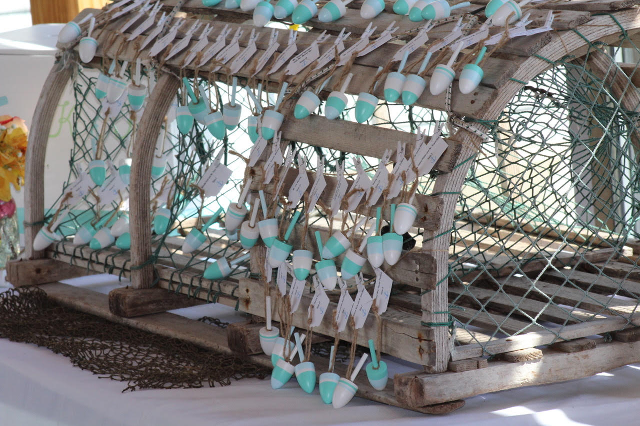 Small lobster buoys adorn a lobster trap and serve as seating cards for guests at a Maine Maritime Museum wedding.